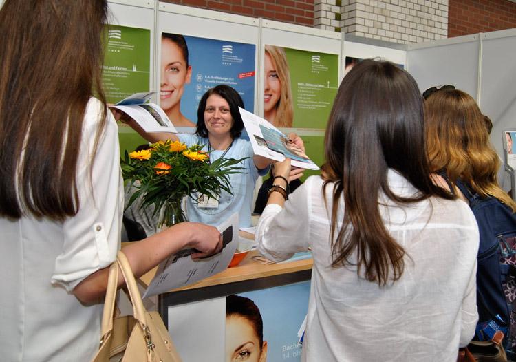 HMKW-Studentin Nicole Schondorf mit Interessierten am Messe-Stand.