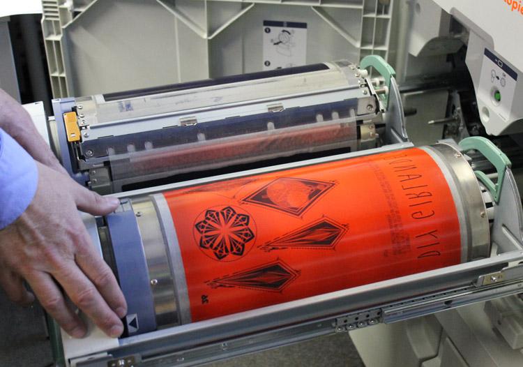 Einsatz einer Druckschablone an der Riso Rotationssiebdruckmaschine.